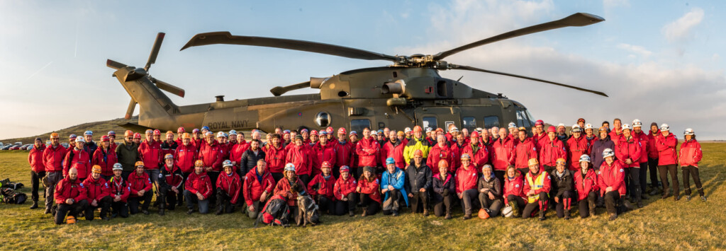 Volunteers of Dartmoor Search and Rescue in front of a Royal Navy Helicopter on Dartmoor